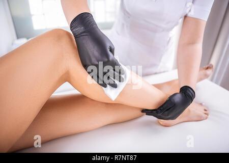 Master in Haarentfernung arbeiten hart, Haare entfernen von Beine - Stockfoto