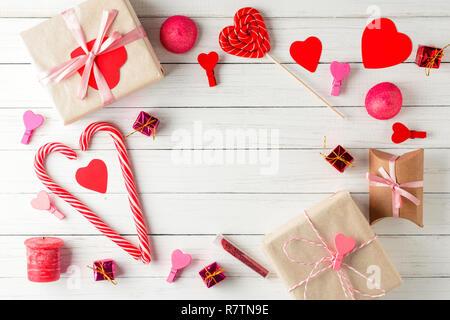 Valentines Tag Hintergrund. Rahmen von roten Herzen, Geschenkbox mit Schleife und Süßigkeiten Süßigkeiten auf weißem Holz- Hintergrund, Ansicht von oben - Stockfoto