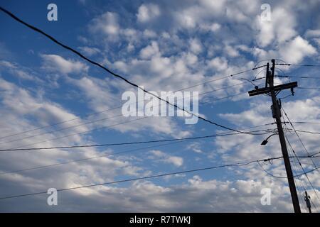 Elektrische Grid Infrastruktur, utility Pole und Overhead Stromleitungen gegen den blauen Himmel und Wolken in Wyoming/USA. - Stockfoto