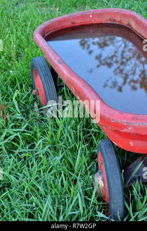 Rote metall Wagen mit Regenwasser gefüllt Verbeult - Stockfoto