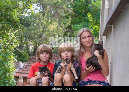 Mutter mit ihren beiden Söhnen, sitzen und halten Katzen - Stockfoto