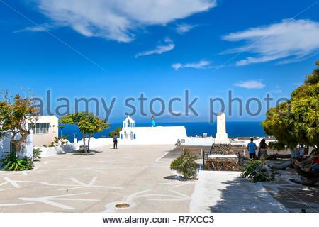 Eine junge Frau stellt auf eine weiße Wand mit Blick auf das Ionische Meer an einem Sommertag in Santorini, Griechenland. - Stockfoto