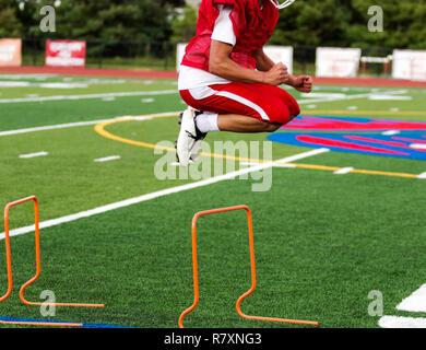 Ein High School Athlet springen über Hindernisse auf grünem Rasen Feld während der Saison Fußball-Praxis. - Stockfoto