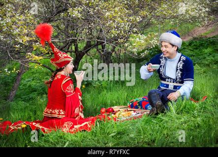 Kasachischen paar Tee trinken auf dem grünen Gras im Apple Garten von Almaty, Kasachstan, Mittelasien - Stockfoto