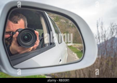 Fotograf, spiegelt sich in dem Auto Spiegel fotografieren während der Fahrt durch die schönen grünen Tal - Stockfoto
