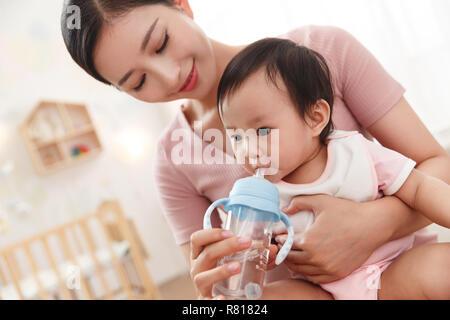 Mutter Einziehen des Babys zu trinken - Stockfoto