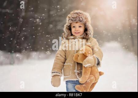 Ein Kind schmücken einen Weihnachtsbaum im Freien. Der junge hängt roten Blasen und isst Lebkuchen. Er ist in einem schaffell Fell gekleidet, im Hintergrund grün - Stockfoto