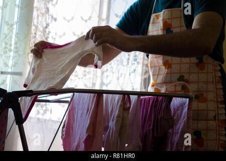 Ein junger Vater das Tragen einer Schürze und hängende Kleidung des Babys auf einen Trockner. Mann Vorbereitung eine Überraschung für seine Frau am 8. März - Stockfoto