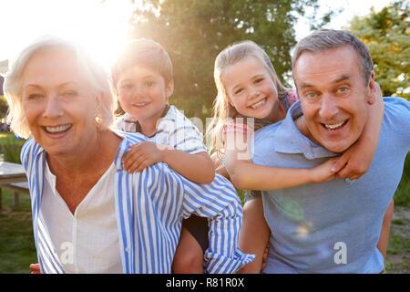 Portrait von lächelnden Großeltern und Enkelkinder Piggyback Ride im Freien im Sommer Park - Stockfoto