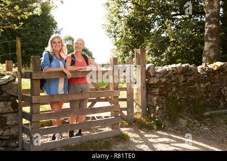 Portrait von älteren Mutter mit Tochter Wandern in Lake District in Großbritannien über hölzerne Tor suchen - Stockfoto