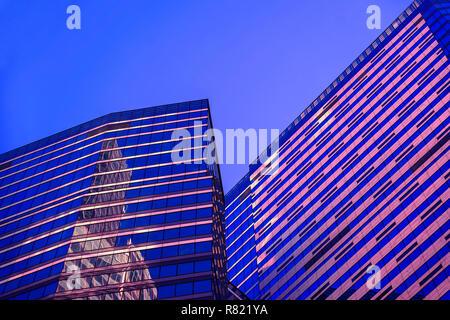 Abstrakte Gebäude bei Nacht, geometrische Muster aus Glas und Beton, Hochhaus, Design mit Reflexion. Städtische Gebäude Hintergrund