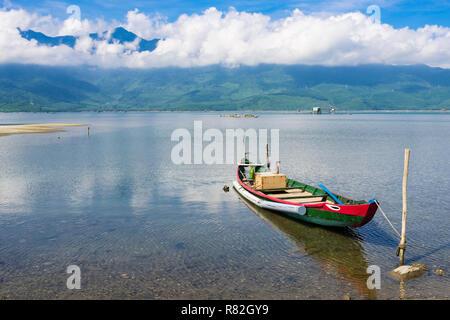 Die kleinen traditionellen Fischerboot auf dem Schoß eine Lagune mit Bergen in Bạch Mã Nationalpark darüber hinaus. Lang Co, Phu Loc, Thua Thien Hue, Vietnam, Asien - Stockfoto