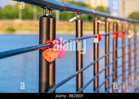 Bunte Metallschlösser hängen schwarz Geländer im Sunrise Licht. - Stockfoto