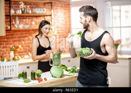 Junge Sport paar Snack mit gesunden Salat und Grünen Smoothie in der Küche zu Hause. - Stockfoto