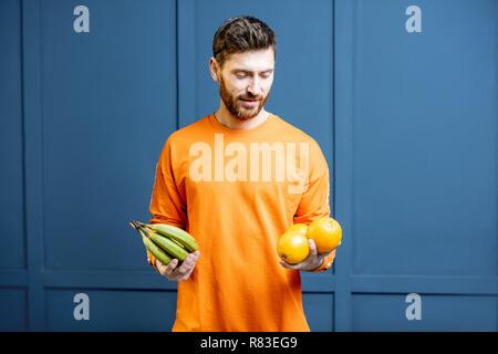Bunte Porträt einer kaukasischen bärtigen Mann in Orange Pullover holding Früchte auf dem blauen Hintergrund - Stockfoto