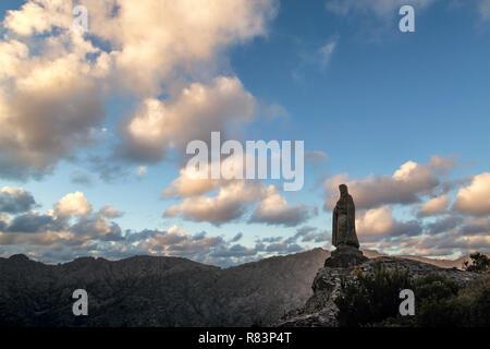 Eine religiöse steinerne Statue auf einem Felsen in der Balagne Korsika mit Bergen in der Ferne montiert - Stockfoto