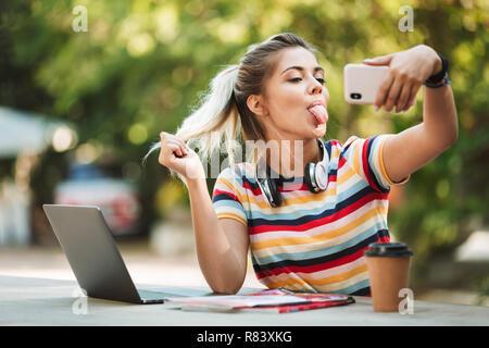 Porträt eines lächelnden jungen Teenager Mädchen am Tisch sitzen mit Laptop im Park, Musik hören mit Kopfhörern, mit Handy - Stockfoto