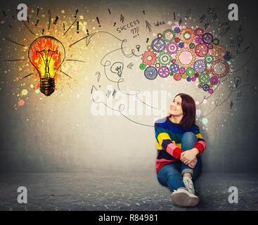 Junge Frau auf dem Boden sitzend lächelnd an einer hellen Lampe an der Wand. Idee, Konzept, das kreative Denken als bunte Gang Gehirn über dem Kopf - Stockfoto