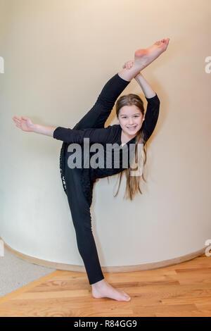 Zehn Jahre alten Tänzerin Mädchen ihre Flexibilität zeigen, indem Sie mit Pfeil und Bogen Bein halten. (MR) - Stockfoto