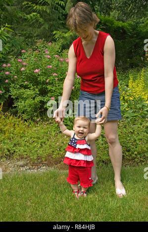 7 Monate alten Mädchen und ihre Mutter ihr hilft laufen lernen. (MR) - Stockfoto