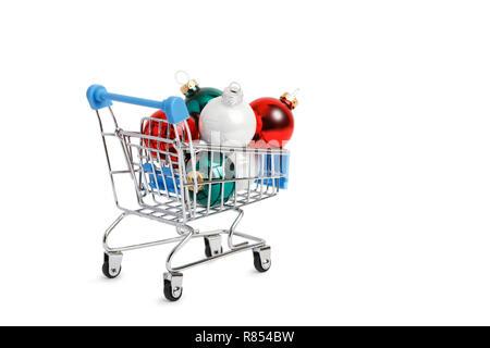 Supermarkt Einkaufswagen mit bunten Weihnachtskugeln isoliert auf Weiss. Copyspace. - Stockfoto