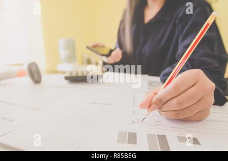 Business Konzept der Finanz- und Rechnungswesen mit der menschlichen Hand halten Smartphone und Schreiben, Finanzen Bericht und mit Blatt Papier von Planungsdaten