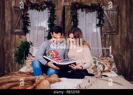Die schöne Zeit zu Hause. Schöne junge Liebende Paar kleben aneinander und lächelnd, während Frau mit einem Buch. - Stockfoto
