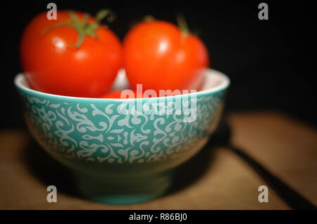 Noch immer leben Kochen, Tomaten in einer Runde Keramik Schüssel mit türkis Design auf ein Holzbrett und ein Löffel. - Stockfoto
