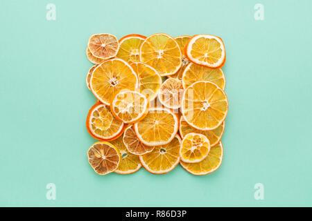 Getrocknet Zitrusfrüchte scheiben Zitronen & Orangen auf Türkis farbigen Hintergrund. Hausgemachte Weihnachten natürliche Dekoration. Quadratisch, Flach. - Stockfoto