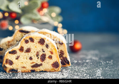 Christstollen auf blau-grünen Hintergrund mit festlichen Weihnachtsbeleuchtung und roten Beeren im Winter, kopieren - Raum. Traditionelle deutsche Dessert für Weihnachten celeb - Stockfoto