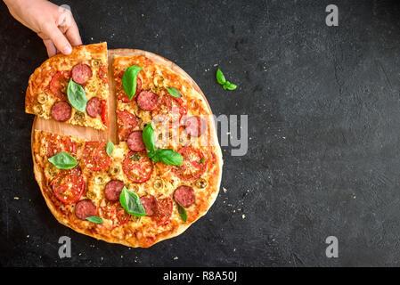 Hand, denn ein Stück italienische Pizza. Italienische Pizza und Hände schließen sich über schwarzen Hintergrund, Ansicht von oben, kopieren. - Stockfoto