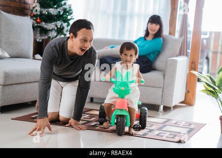 Portrait von Glück Tochter mit Vater mit Dreirad und Mutter sitzen auf einer Couch hinter - Stockfoto
