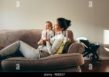 Junge Frau liegt auf einem Sofa ihr Kind halten. Lächelnde Mutter kümmert sich um ihr Baby zu Hause. - Stockfoto