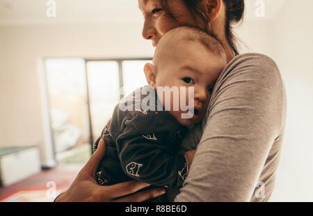 Seitenansicht einer Mutter mit ihrem Baby in ihr Zimmer. Nahaufnahme einer glücklichen Mutter ihr Baby an ihrer Brust zu Hause halten. - Stockfoto