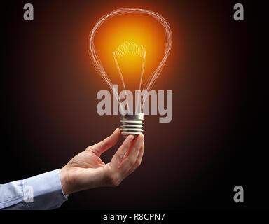 Hand, die Glühbirne auf dunklem Hintergrund. Neue Idee Konzept - Stockfoto