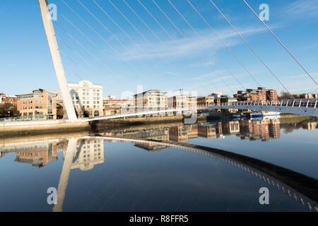 Gebäude auf Newcastle Quayside von Gateshead Millennium Bridge gerahmt und in den Fluss Tyne, North East England, UK wider - Stockfoto