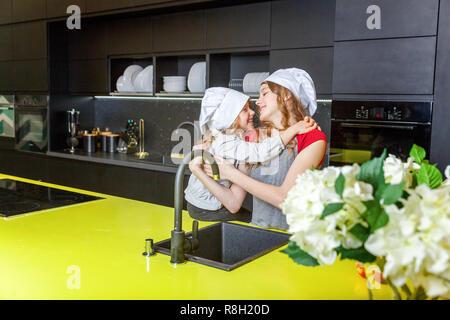 Zwei Mädchen mit Küchenchef hat sich umarmen und Spaß in der Küche. Schwestern kleines Kind und Teenager Kochen gesund essen zu Hause. Kindheit, Familie, househ - Stockfoto