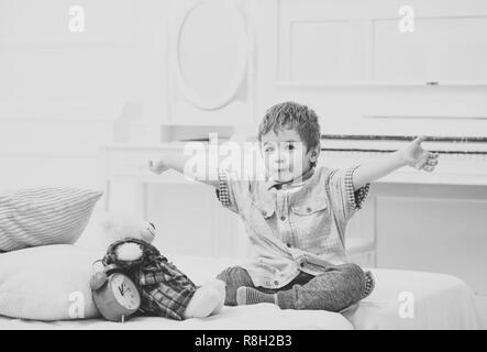 Kind im Schlafzimmer Märchen erzählen für Spielzeug. Märchen Konzept. Kid, Plüschbär in der Nähe von Kissen und Wecker, luxuriöse Innenausstattung Hintergrund. Junge mit Lieblingsspielzeug auf dem Bett, Wünsche süße Träume. - Stockfoto