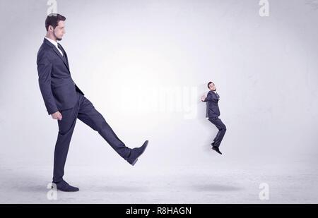 Großer Mann in Anzug, treten kleine, sich mit einfachen, weißen Tapeten - Stockfoto