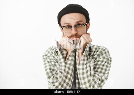 Nahaufnahme des dummen niedlich aussehenden Freund in Schwarz beanie Brillen und Grünen kariertes Hemd schiefen Kopf auf Palmen Schmollen und Falten Lippen, zärtlich und unschuldiger Blick an Charme, Freundin - Stockfoto