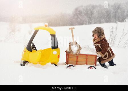 Happy Little Boy in Winterkleidung. Das Kind ist Spielen im Freien im Winter. Ein gelbes Spielzeugauto und eine kleine Warenkorb gefüllt mit Schnee, im Schnee stecken - Stockfoto