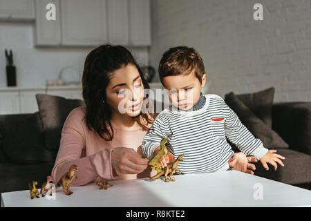 Konzentrierte sich Frau und kleinen Jungen spielen Spielzeug Dinosaurier am Tisch im Wohnzimmer zu Hause - Stockfoto