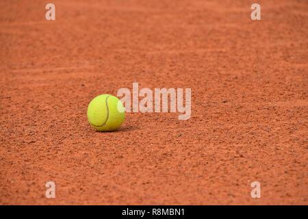 Nahaufnahme einer gelben Filz Tennis ball auf rot braun Ton Boden Court, Low Angle View - Stockfoto