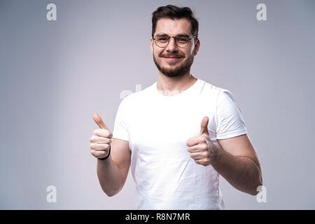Porträt eines lächelnden Mann mit Daumen hoch über grauen Hintergrund. - Stockfoto