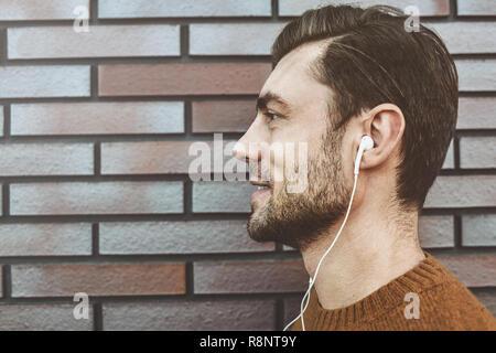 Foto von stilvollen hübscher junger Mann mit Borsten stehend im Freien. Mann, braun Pullover. Lächelnde Menschen hören von Musik über Kopfhörer und Leanin - Stockfoto