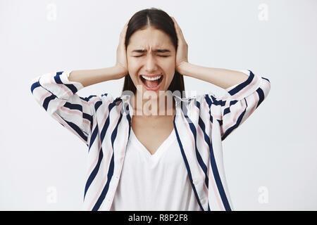 Innen- schuss von bis verärgert europäische Frau in gestreifte Bluse gefüttert, das Kreischen von Depression, die Ohren mit Palmen mit geschlossenen Augen, schreien, Befreiung von Stress, ständigen intensiven Über grauer Hintergrund - Stockfoto