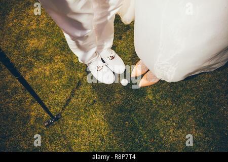 Paar in der Hochzeit Kleidung, Golf zu spielen. Beine auf grünem Gras - Stockfoto
