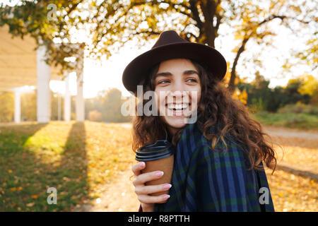 Schöne junge Frau mit Hut Wandern im Park im Herbst, die Tasse Kaffee zum Mitnehmen - Stockfoto