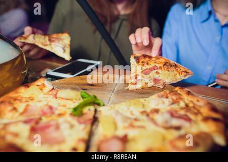 Hände, die Scheiben Pizza Margherita. Pizza Margarita und Hände schließen sich über schwarzen Hintergrund. - Stockfoto