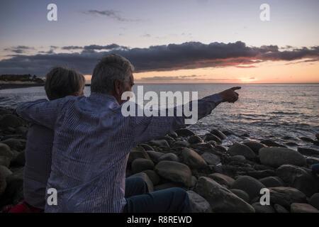 Romantik Aktivität für Erwachsene senior Paar am Strand sitzen auf der Suche einen farbigen Sonnenuntergang am Meer - Ferienhäuser und liebe Konzept für reifer Mann und woma - Stockfoto